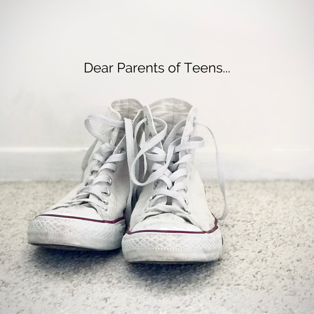 A pair of high top tennis shoes on the ground with the words Dear Parents of Teens written on the wall.
