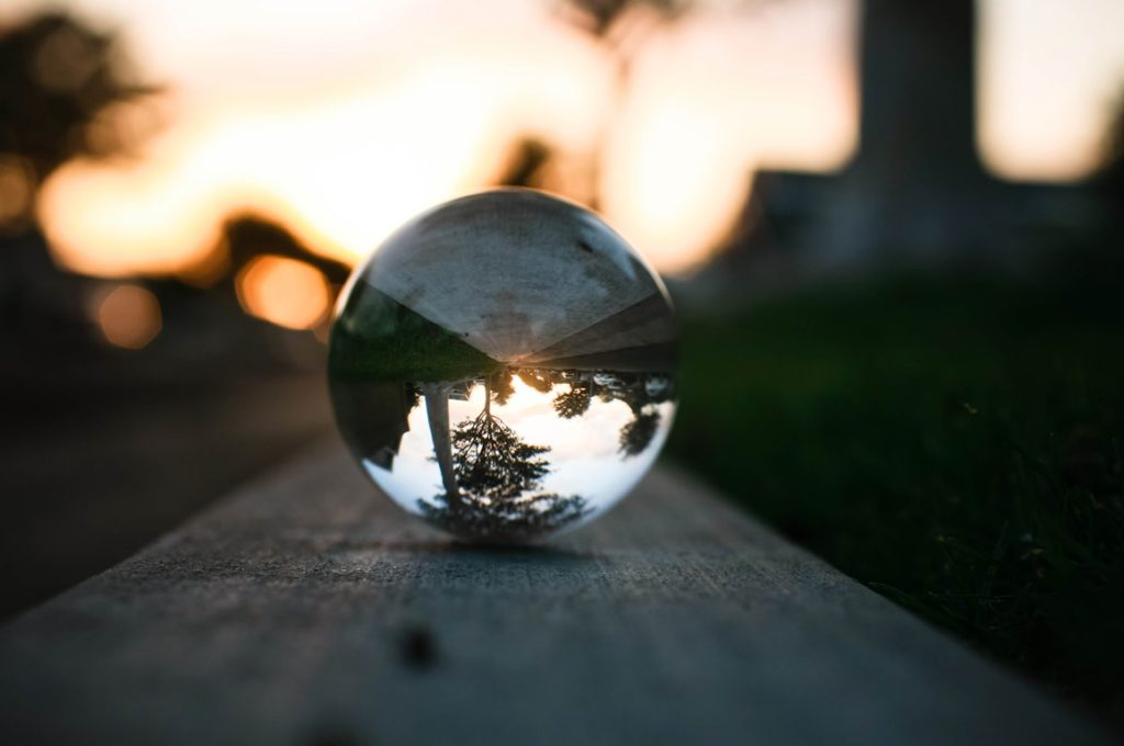 A Lensball containing an image of a tree with the sunset in the background